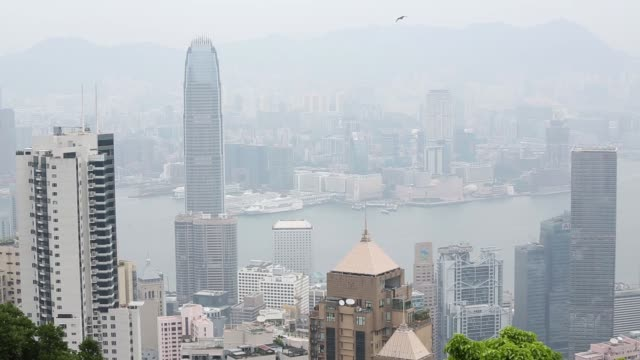 Tourists take photographs from Victoria Peak as commercial and residential buildings stand in the distance in Hong Kong China on Thursday July 9...