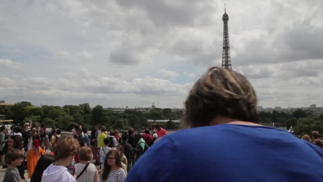 Tourists take photographs in front of the Eiffel Tower in Paris France on Saturday Aug 9 Tourists take in a view of the Eiffel Tower Wide shots...