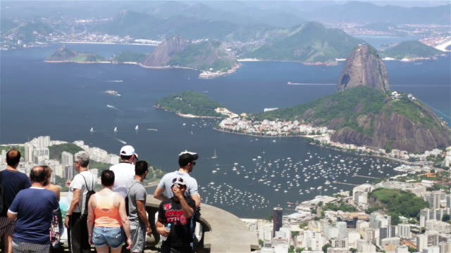 LS, HA Tourists take photographs of Rio skyline from Christ the Redeemer statue at Corcovado / Rio de Janeiro, Brazil