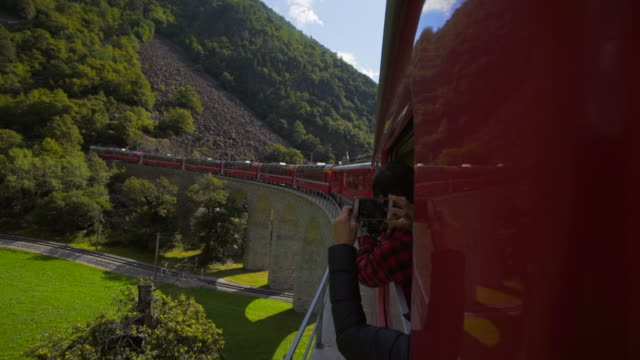 vidéos et rushes de tourists take photos of side of red train and rugged mountains with cell phones - swiss alps, switzerland - filmer