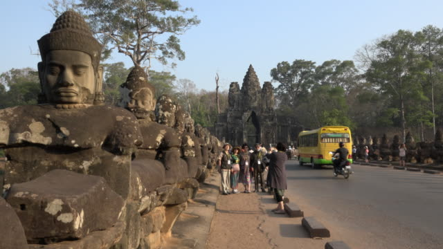 tourists take photos of south gate, entrance of angkor thom - cambodia stock videos and b-roll footage
