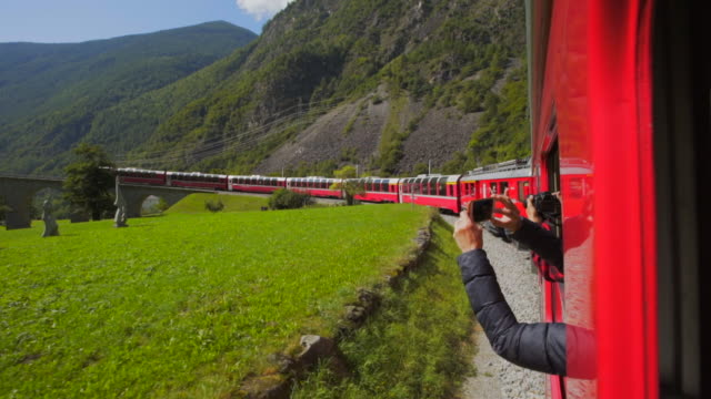 stockvideo's en b-roll-footage met tourists take photos of the stunning scenery of the bernina pass from window of red train - swiss alps, switzerland - passenger train