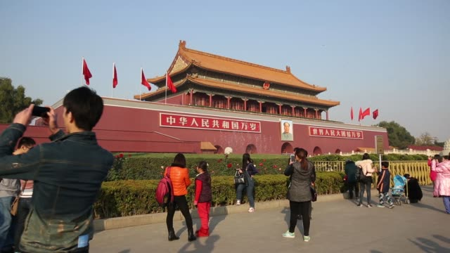 vídeos de stock, filmes e b-roll de tourists take pictures in front of tiananmen gate in beijing china on sunday nov 9 a guard stands in front of a large portrait of chairman mao zedong... - portão da paz celestial de tiananmen