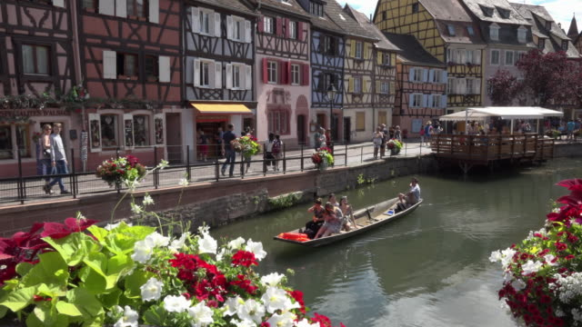 Tourists taking a boat ride in La Petite Venise on idyllic river Lauch