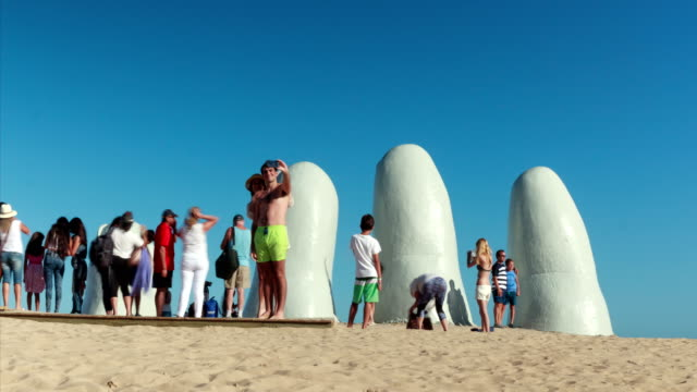 "vídeos de stock, filmes e b-roll de tourists taking photos in ""fingers monument"" in punta del este, uruguay - uruguai"
