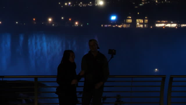 tourists taking photos of the color change of niagara falls at night amidst the 2020 global coronavirus pandemic. - active lifestyle stock videos & royalty-free footage