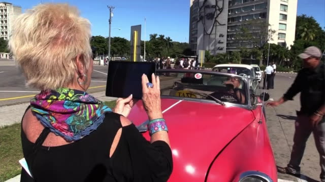 Tourists taking photos with a classic car parked on the road
