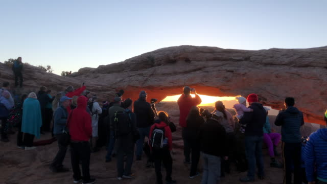 tourists taking picture in the morning in the canyonlands national park in america - natural arch stock videos & royalty-free footage