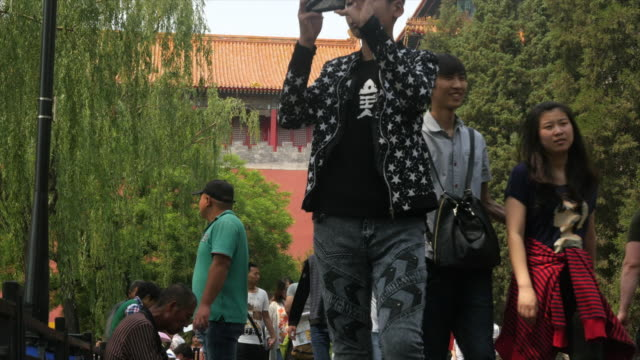 Tourists taking picture with cell phone outside of Forbidden city in Beijing, China