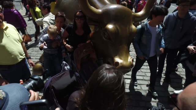 tourists taking picture with sculpture bull at downtown financial district - photographing stock-videos und b-roll-filmmaterial