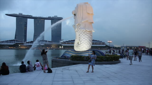 tourists taking pictures in merlion park, singapore. - merlion fictional character stock videos and b-roll footage