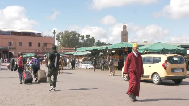 tourists, taxis and activity on djemaa el fna showing koutoubia minaret, marrakech, morocco, north africa, africa - circa 12th century stock videos & royalty-free footage