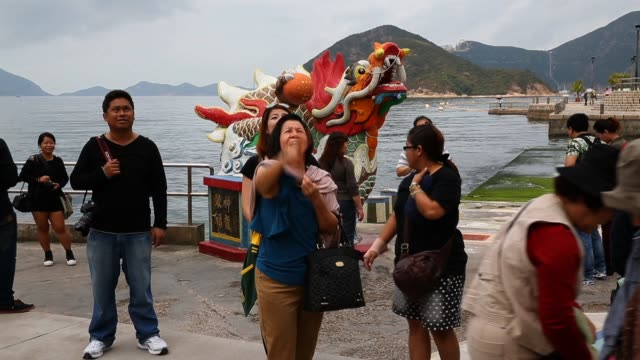 Tourists throw coins into a wishing well at the Kwun Yam Shrine At Repulse Bay on March 20 2013 in Hong Kong Hong Kong Located at the Southern end of...