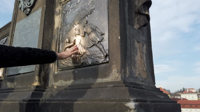 tourists touching the reliefs at the statue of st. john of nepomuk on charles bridge - john fortune stock videos & royalty-free footage