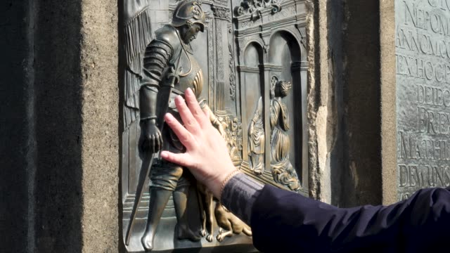 tourists touching the statue on the charles bridge prague for good luck - memorial plaque stock videos and b-roll footage