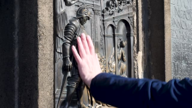 Tourists touching the Statue on the Charles Bridge Prague for Good Luck