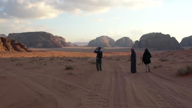 vídeos de stock, filmes e b-roll de tourists trekking through wadi rum desert wilderness early in the morning, jordan - local de filmagem não americano