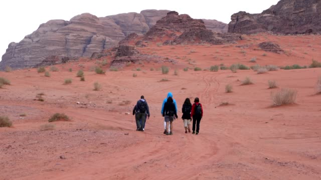 stockvideo's en b-roll-footage met tourists trekking through wadi rum desert wilderness early in the morning, jordan - fysische geografie