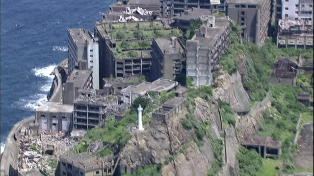 Tourists use a concrete sidewalk as they visit the ruins on abandoned Hashima Island.