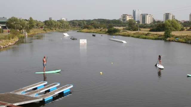 tourists use sup in the neighbourhood vsestra hamnen with harbor on july 29, 2019 in the city of malmö in sweden. - オーレスン海峡点の映像素材/bロール