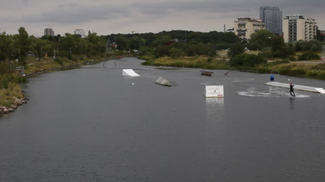 tourists use wake board in the wake park in the neighbourhood vsestra hamnen with harbor on july 29, 2019 in the city of malmö in sweden. - オーレスン海峡点の映像素材/bロール
