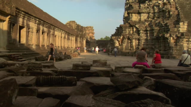 pan tu tourists view temple interior at angkor wat / cambodia - besichtigung stock-videos und b-roll-filmmaterial