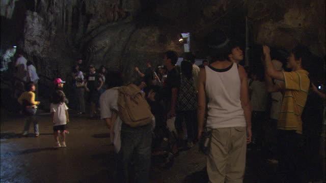 tourists visit akiyoshi cave and admire the stalactites. - 史跡めぐり点の映像素材/bロール