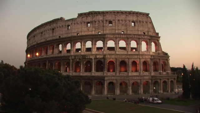 vidéos et rushes de tourists visit the colosseum as lights illuminate the arches at night. - gladiateur