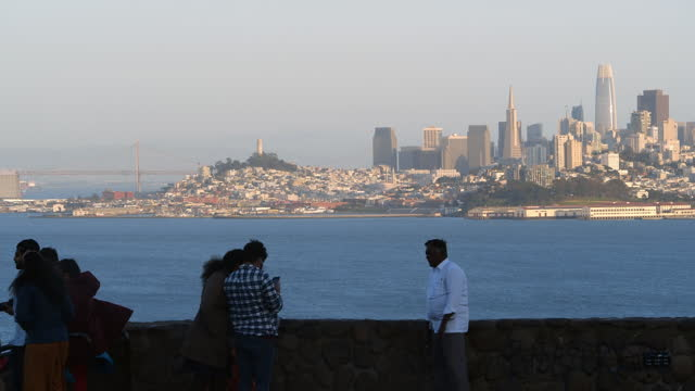 tourists visit the golden gate bridge in san francisco at sunset and take pictures amid the coronavirus pandemic. - indian ethnicity stock videos & royalty-free footage