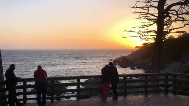 tourists visit the lone cypress and enjoy sunset amid the covid-19 pandemic in pebble beach, california on march 21, 2021. - horizon over water stock videos & royalty-free footage