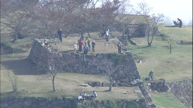 tourists visit the ruins of the takeda castle on a mountaintop in japan. - 遺跡点の映像素材/bロール