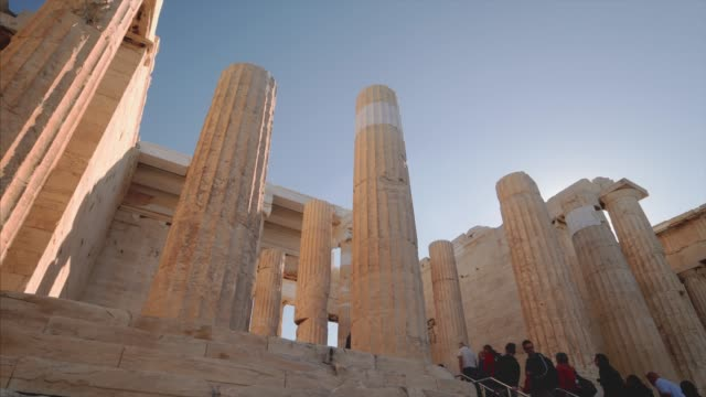 tourists visiting ancient greek ruins of the propylaia at the acropolis in athens, greece - mythologie stock-videos und b-roll-filmmaterial