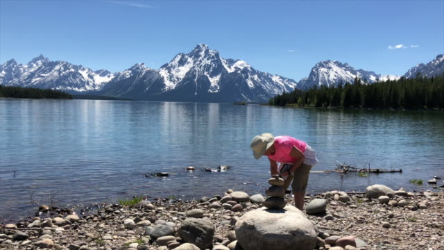 tourists visiting grand teton area in wyoming, usa. lady stacking up pebbles at the bank of jackson lake. - grand teton stock videos & royalty-free footage