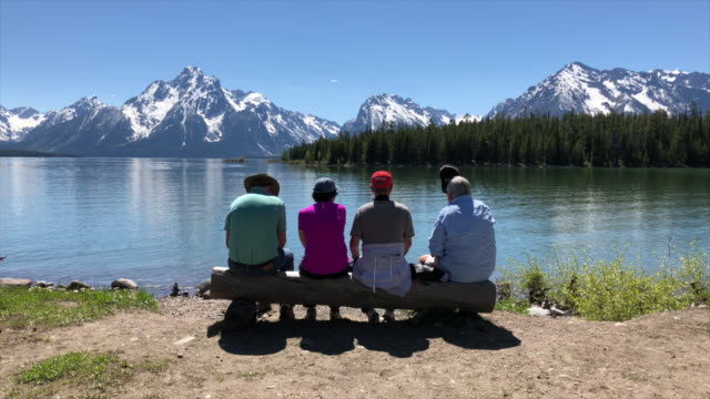 tourists visiting grand teton area in wyoming, usa, sitting on bench enjoying the grand teton mountain and the lake view in the afternoon. - grand teton stock videos & royalty-free footage