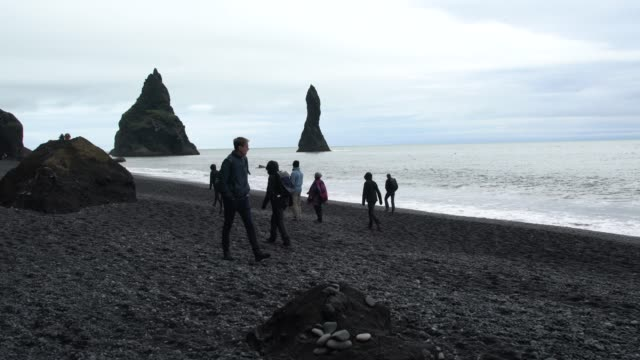 tourists visiting reynisfjara, the world-famous black volcanic beach in south iceland - basalt stock videos & royalty-free footage