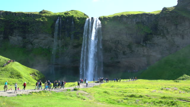 Tourists visiting Seljalandsfoss waterfall in Iceland during a sunny bright day