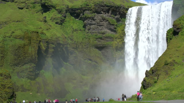 Tourists visiting Skógafoss waterfall in Iceland during a sunny bright day