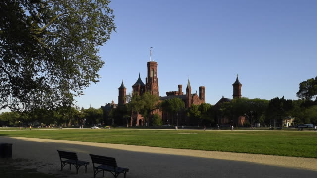 Tourists visiting the National Mall walk past the Smithsonian Castle.