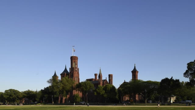 tourists visiting the national mall walk past the smithsonian castle. - smithsonian institution stock videos & royalty-free footage