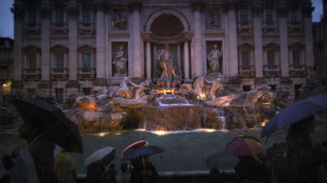 tourists visiting the trevi fountain at dusk in the rain - dolly shot stock videos & royalty-free footage