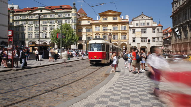 vídeos de stock, filmes e b-roll de tourists wait and board red trams from a median in prague. - stare mesto
