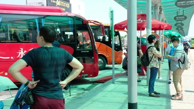 Tourists wait to catch shuttle buses to various casinos in Macau China on Wednesday Sept 27 Tourists board a shuttle bus to a casino in Macau People...