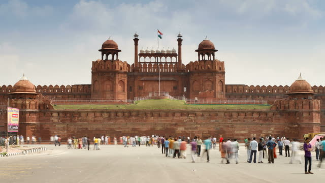 tourists walk about the courtyard in front of the lahore gate in front of the red fort in old delhi. - lahore stock videos and b-roll footage