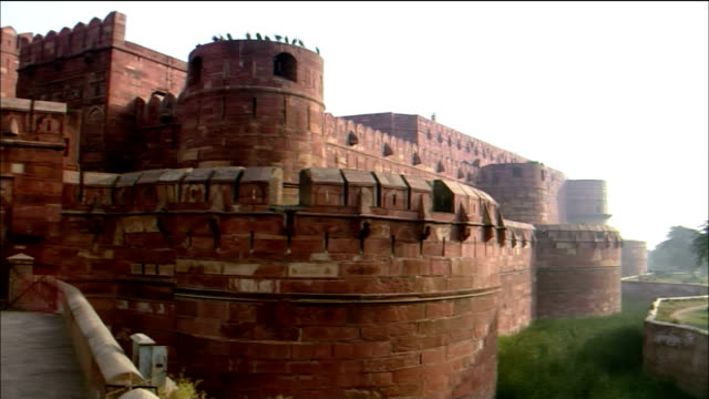 tourists walk along a bridge at the agra fort in india. - mughal empire stock videos and b-roll footage
