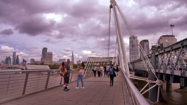 tourists walk along bridge. business and finance. office buildings. london, uk - suspension bridge stock videos & royalty-free footage