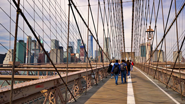 tourists walk along brooklyn bridge. sightseeing. financial manhattan district. freedom tower. corporate offices. landmark. - suspension bridge stock videos & royalty-free footage