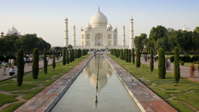 vídeos de stock e filmes b-roll de tourists walk along pristine landscaping leading to the taj mahal. - taj mahal