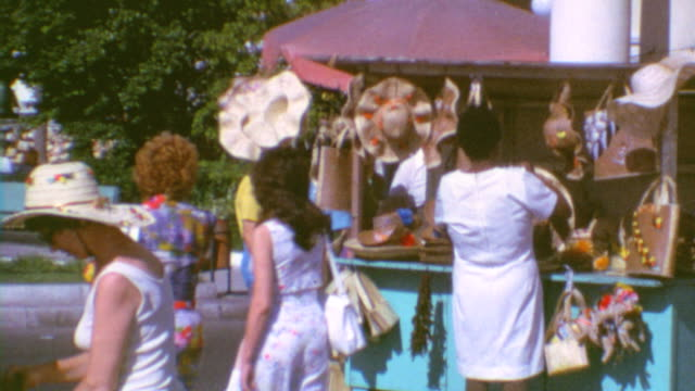 tourists walk along shops in the bahamas / woven goods are displayed / tourist shops on august 02, 1972 in nassau, bahamas - bahamas stock-videos und b-roll-filmmaterial