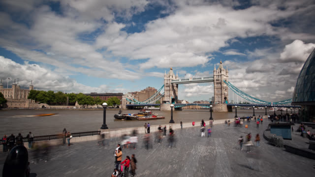 tourists walk along the waterfront next to the tower bridge in london. - ferry stock-videos und b-roll-filmmaterial
