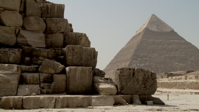 tourists walk among the ancient pyramids in the giza necropolis. available in hd. - pyramide bauwerk stock-videos und b-roll-filmmaterial